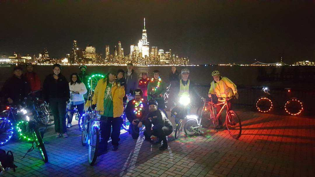 A group of riders stand with their bikes covered in lights in front of the Hudson River and night time New York City skyline.